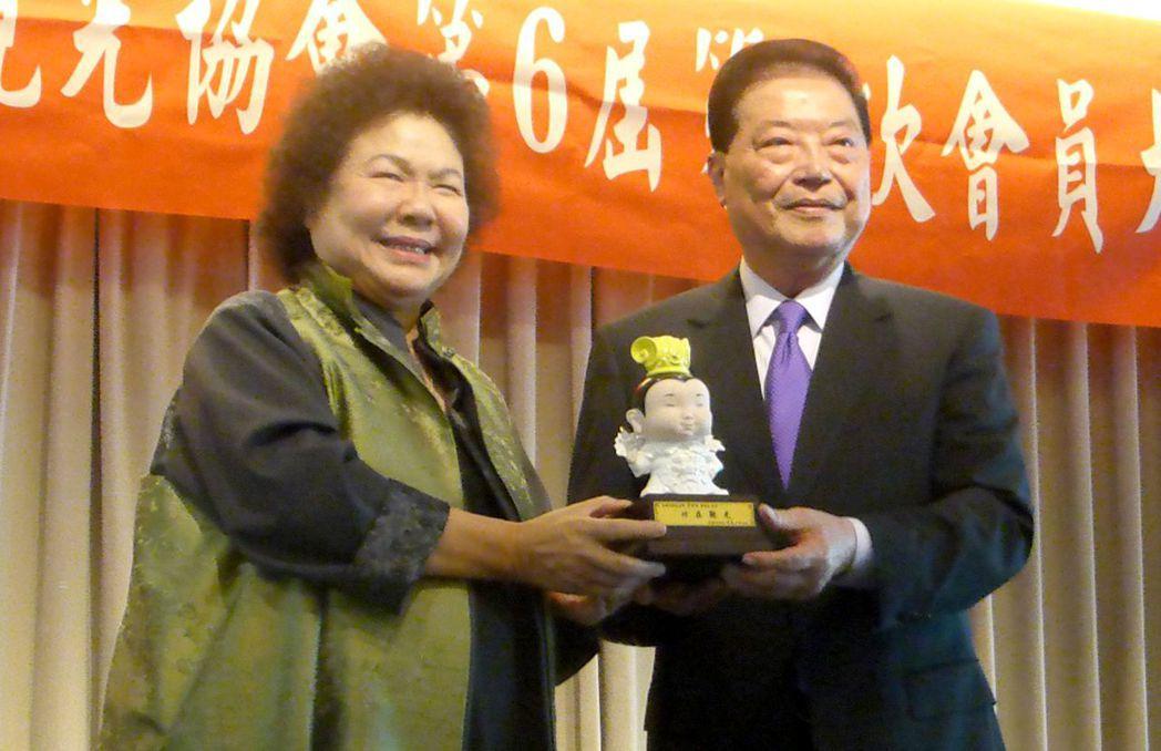 高雄市長陳菊(左)今天贈送一尊三太子給卸任的高雄市觀光協會理事長黃金祥,感謝黃金...