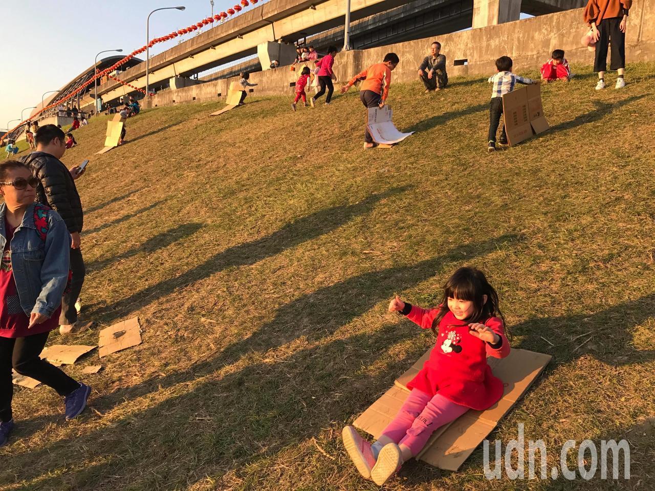 大台北都會公園的河堤土坡竟成滑草道,小朋友將紙箱拆開變成滑草板,造成草皮光禿禿。...