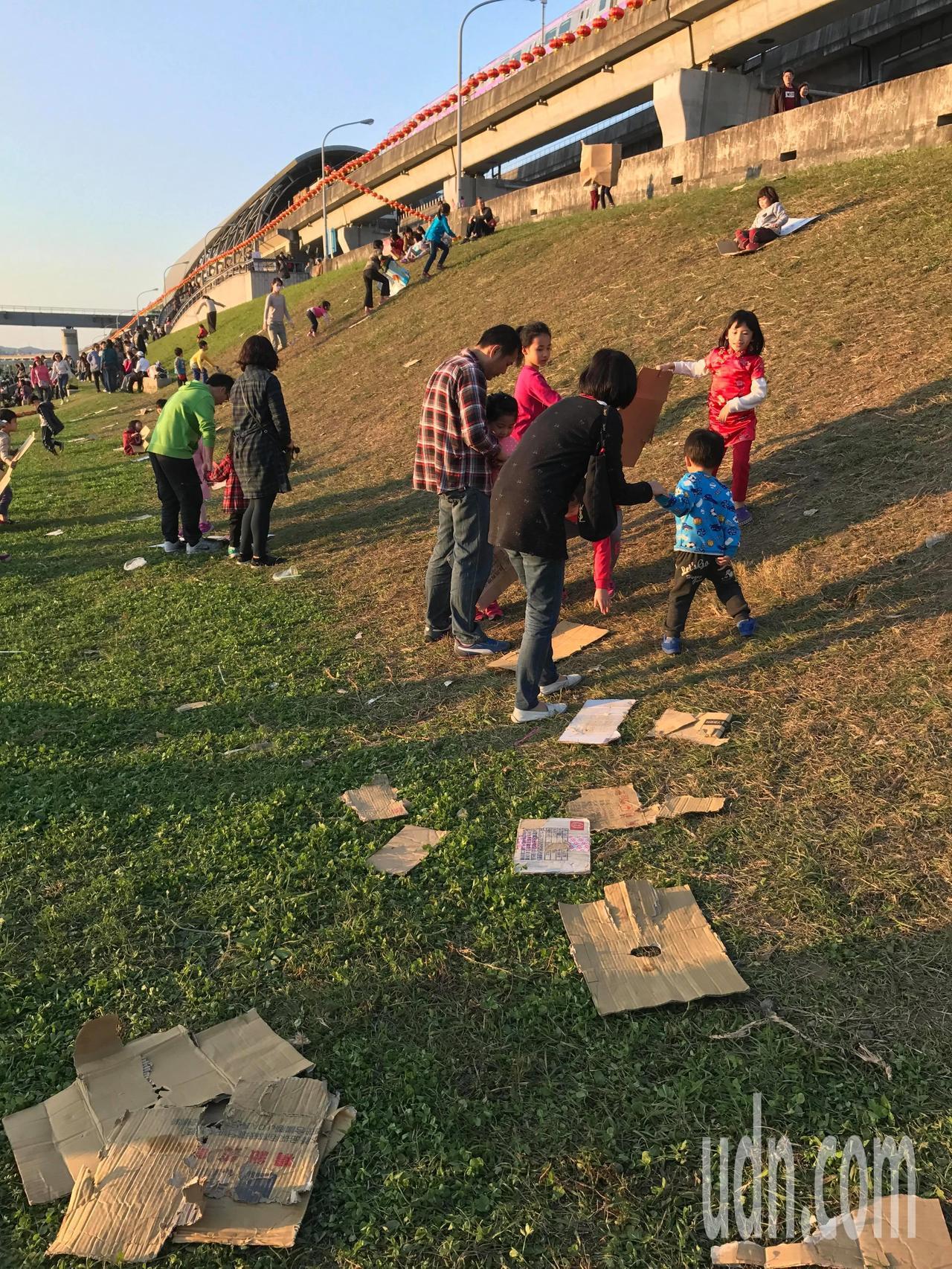大台北都會公園的河堤土坡竟成滑草道,小朋友將紙箱拆開變成滑草板,造成草皮光禿禿,...