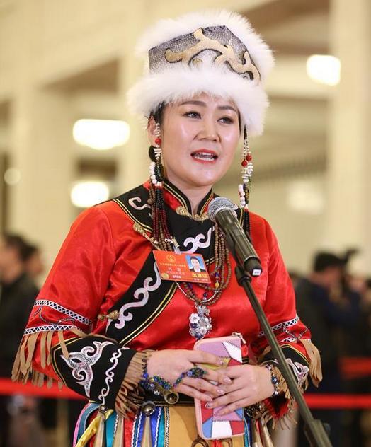 黑龍江省同江鎮中心校教師劉蕾,展示了赫哲族的傳統手工藝品——魚皮包。取自中國網
