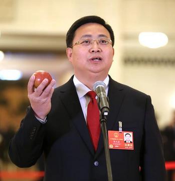 雲南省昭通市市長郭大進秀出手中的紅蘋果說是「金蘋果」。取自中國網