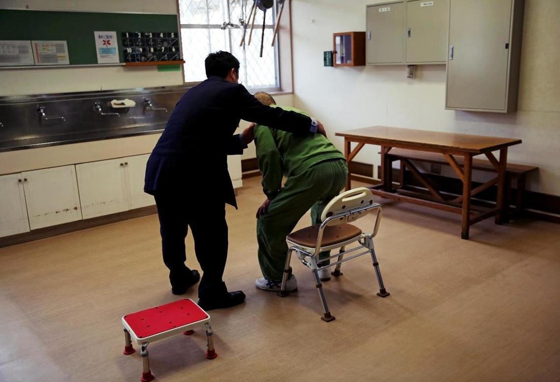 位於日本德島縣的山區裡,一名老人在看護人員的協助下,正在進行每日例行的健康運動—...