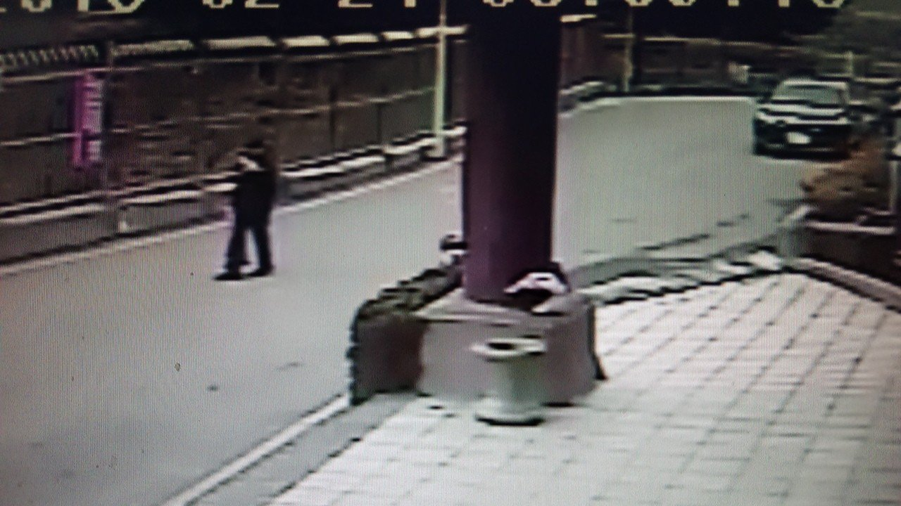 王男抱著一大包偷來的水果離開殯儀館。記者卜敏正/翻攝