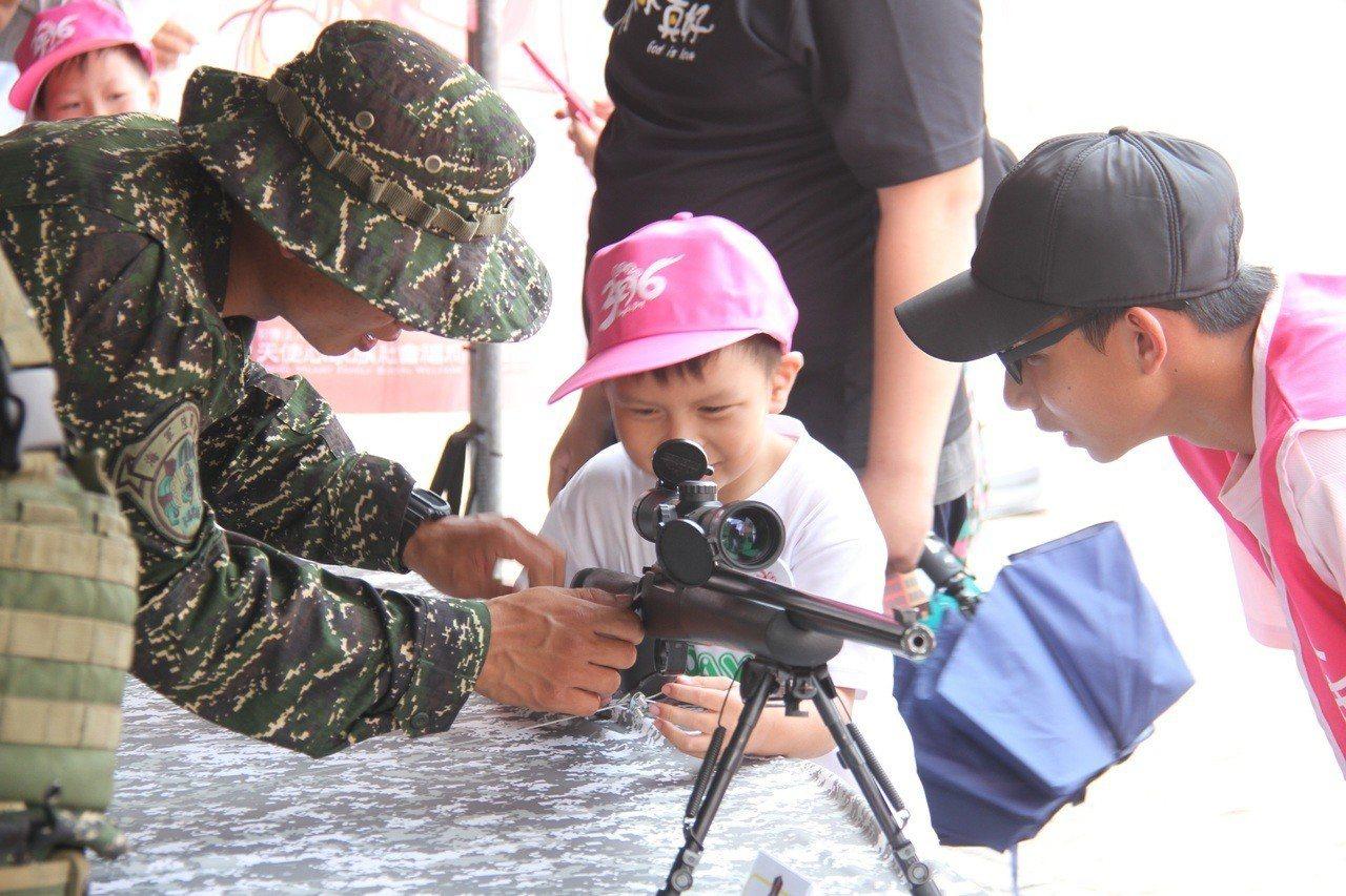 陸戰隊官兵向小朋友介紹狙擊槍。圖/軍聞社