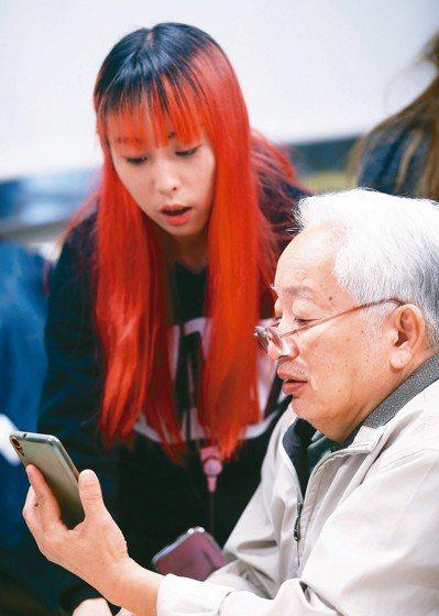 22歲黃奕瑋(左)教69歲的馮鋼上臉書,紅髮老師與白髮學生是世代文化反哺。 記者...