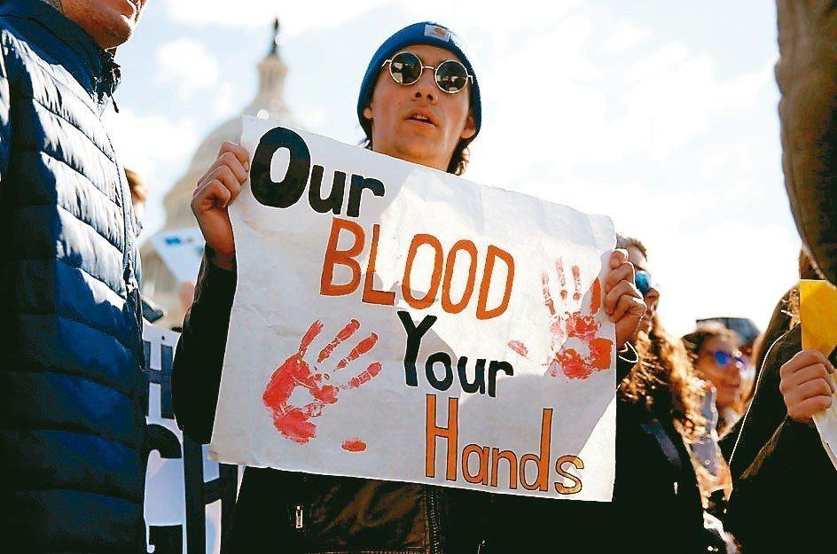 華府學生手持寫有「你的雙手沾染我們的血」的海報,呼籲限槍。 路透
