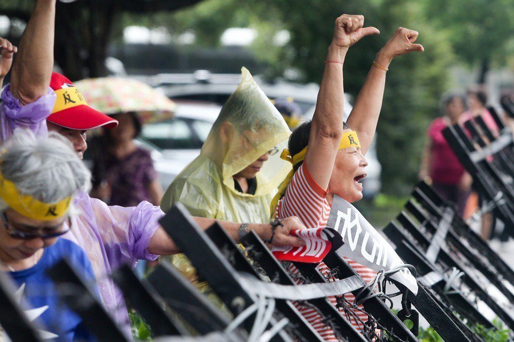 圖為當時抗議年金改革民眾隔著鐵拒馬用手勢表達不滿。 圖/聯合報系資料照片