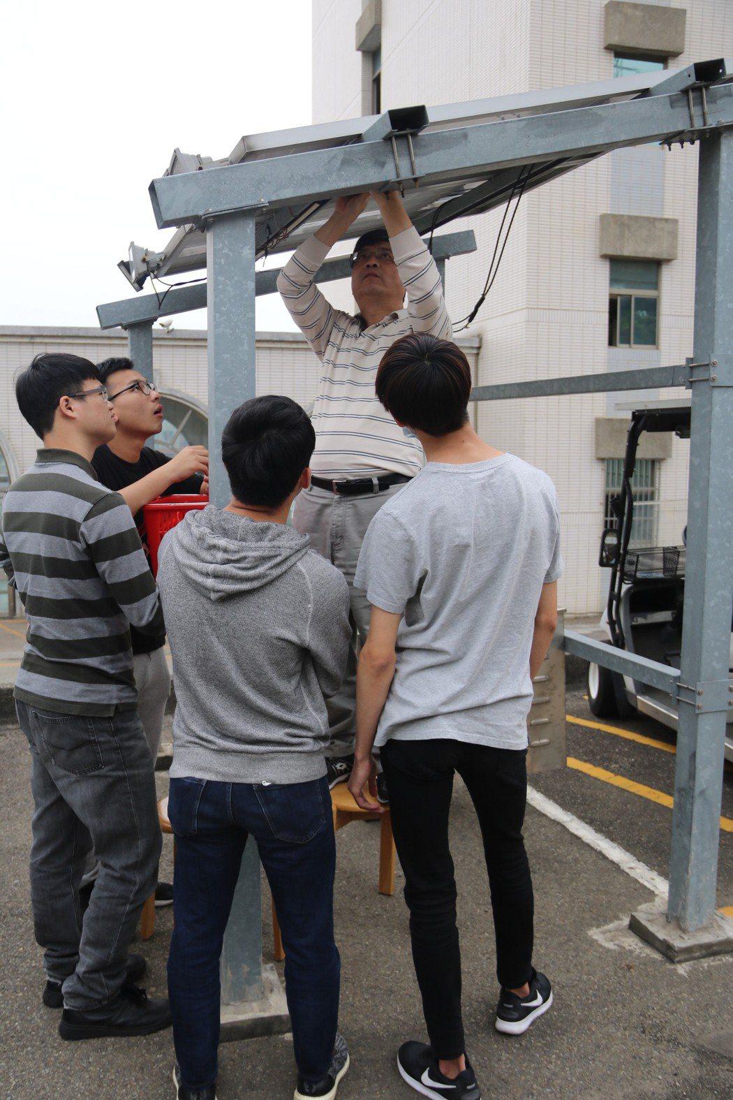 助理教授嚴坤龍(中)向學生解說太陽能光電設備拆卸要領。 弘光科大/提供。