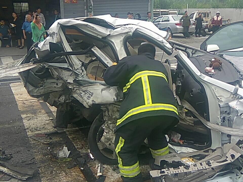 其中一輛白色自小客車慘遭撞擊嚴重,消防人員出動破壞器材才將受困民眾救出送醫。圖/...