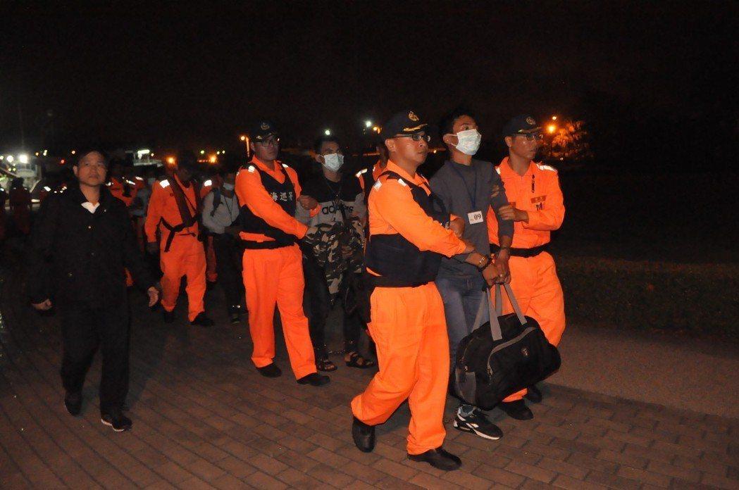金春財號漁船上16名越南偷渡客及6名船員一一點名下船後,在岸邊碼頭上銬,帶至隊上...