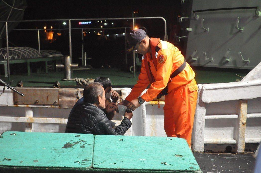 海巡人員為金春財號漁船王姓船長送上口罩。記者黃宣翰/攝影