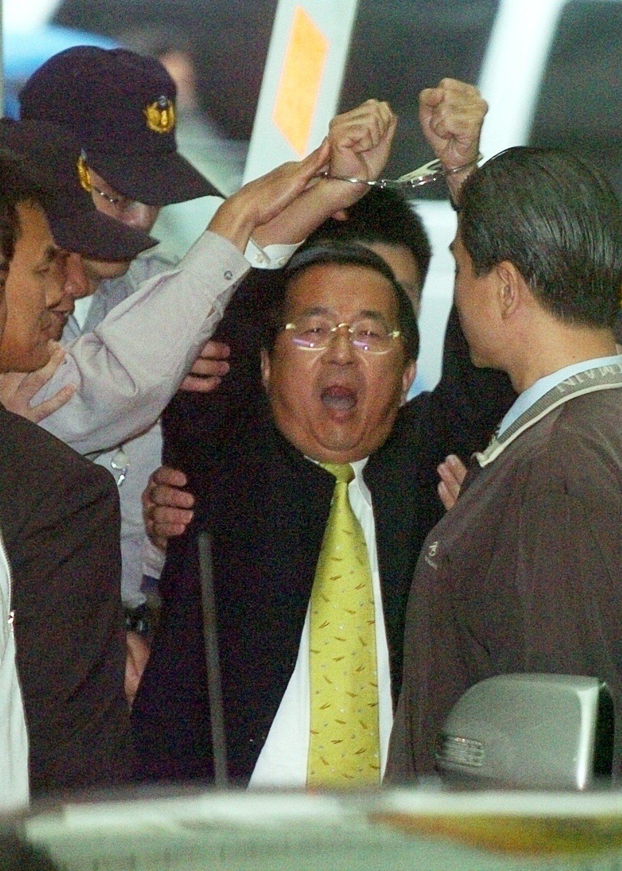 當時陳水扁被上手銬收押,高舉雙手喊「司法迫害」。聯合報系資料照