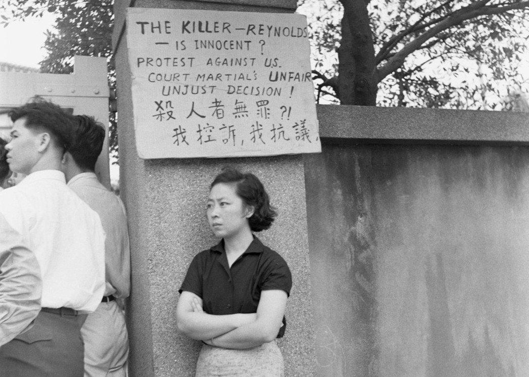 劉自然妻子手持一塊硬紙板到美國大使館門前,她將紙板豎立在路旁,上頭寫著「殺人者無...