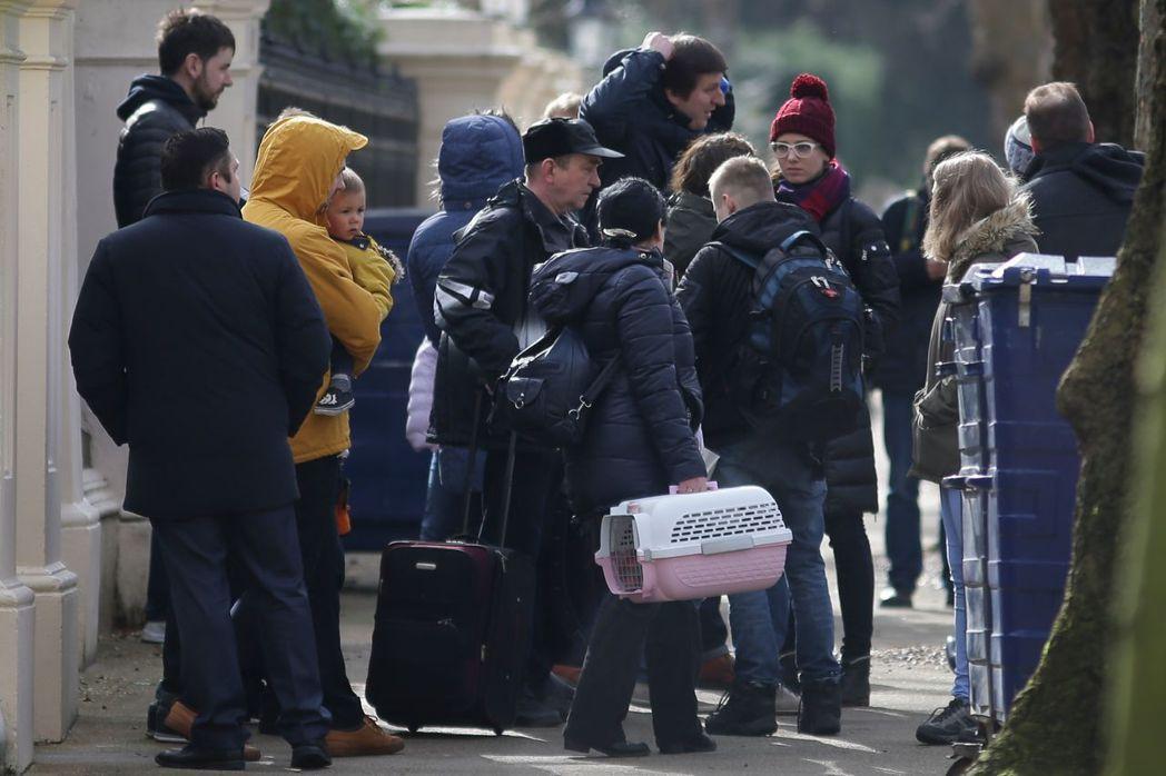 被英國驅逐的俄羅斯外交人員,20日帶著行李走出倫敦的俄國大使館。(法新社)