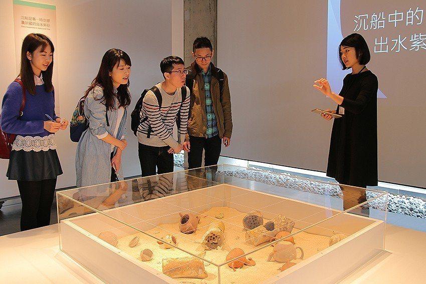 策展團隊中的胡幼函(右)認真地說明有關出水紫砂壺的歷史。 陶博館/提供