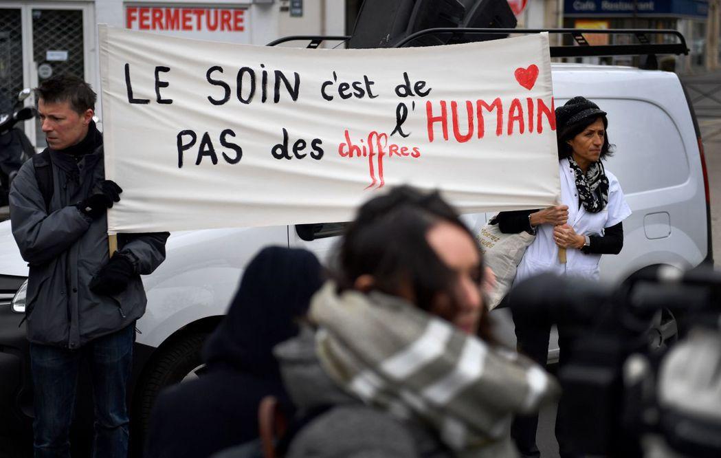 一批法國醫生和護理人員20日在衛生部門前示威,扯起「關愛人類,而不是數字」布條,...