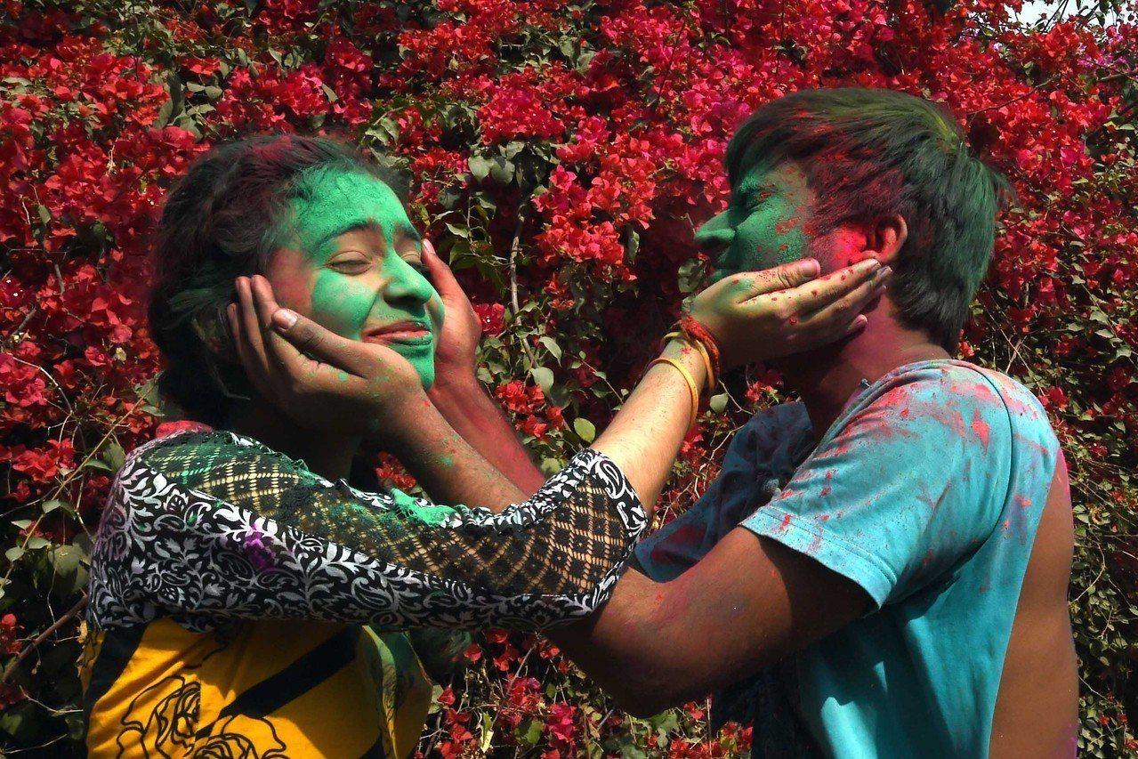 在印度首都新德里的尼赫魯大學校園內,兩名學生參加灑紅節慶祝活動。灑紅節也叫胡裏節...