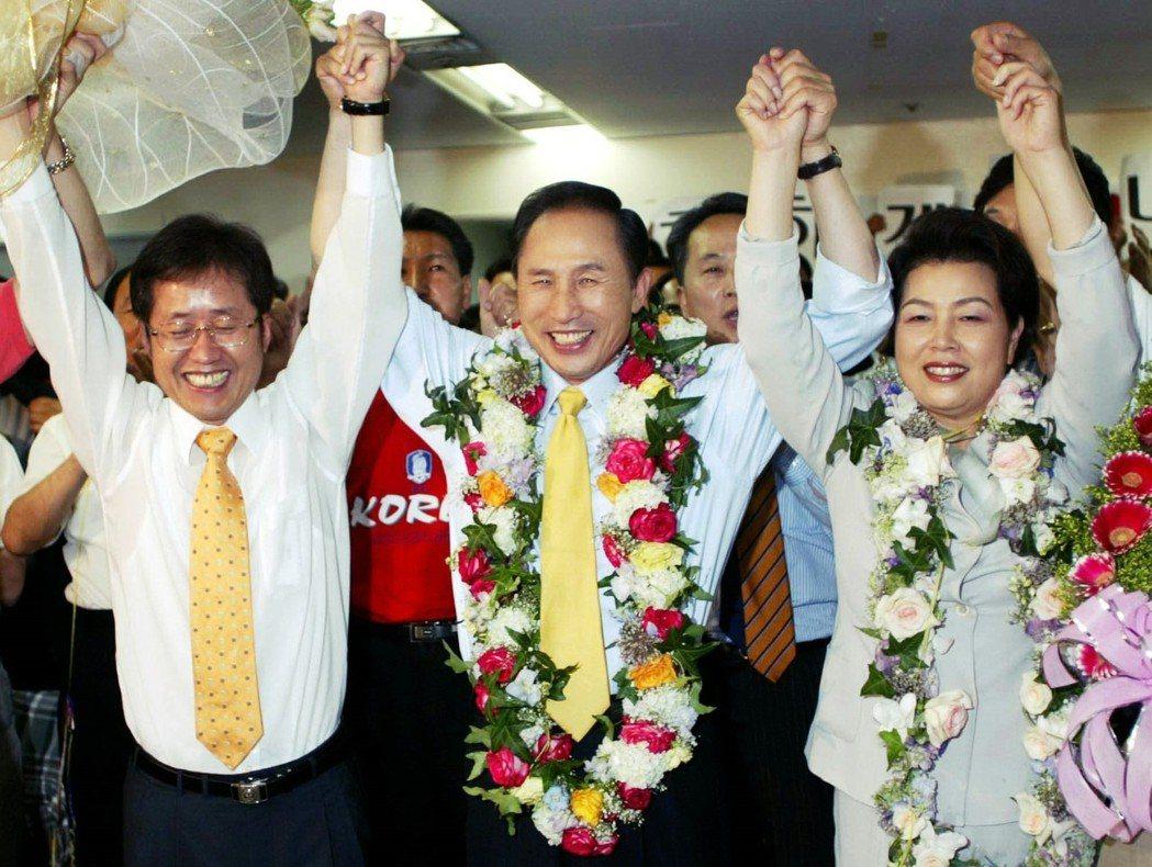 2002年,參選首爾市長的李明博勝選。圖為慶祝勝利的洪準杓(左)、李明博(中)與...