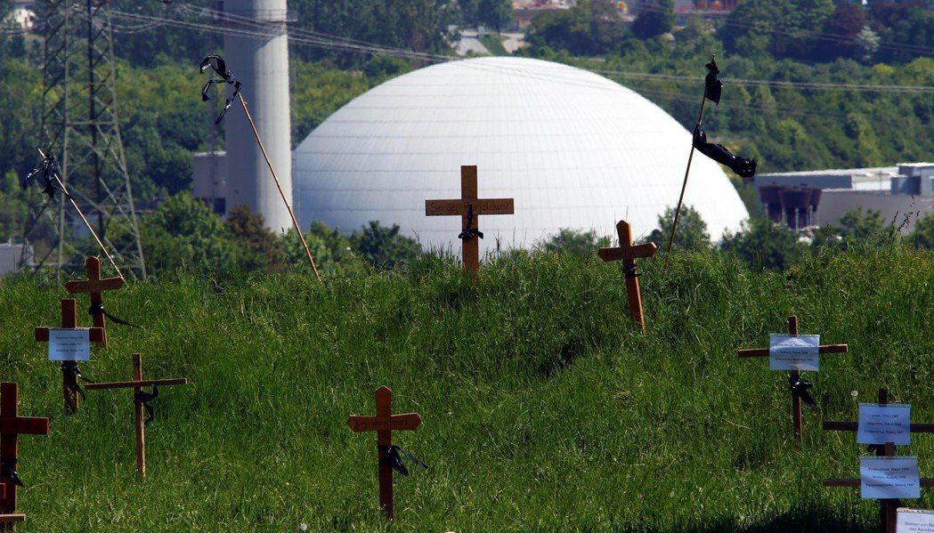 圖為Neckarwestheim核電廠,反核人士在核電廠前豎立木十字架紀念在車諾...