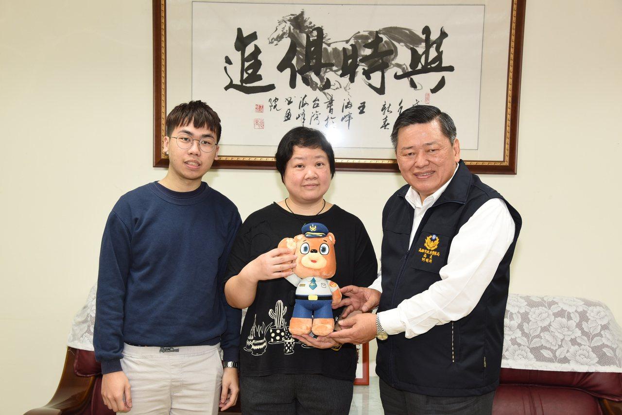 高雄市警局長何明洲親頒「熊古力」公仔給朱小姐母子。圖/高雄市警局提供