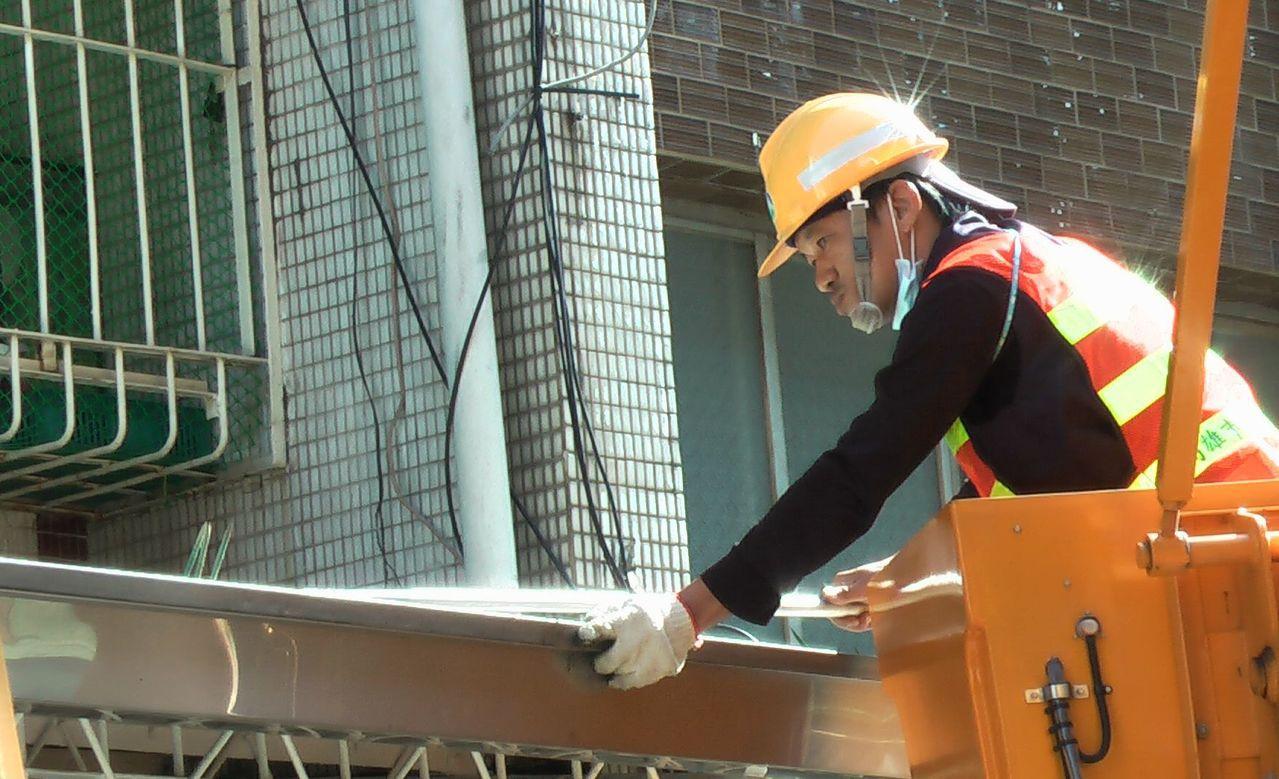屋簷溝高空作業車清潔人員,協助清除簷溝積存的落葉、垃圾。記者徐如宜/攝影
