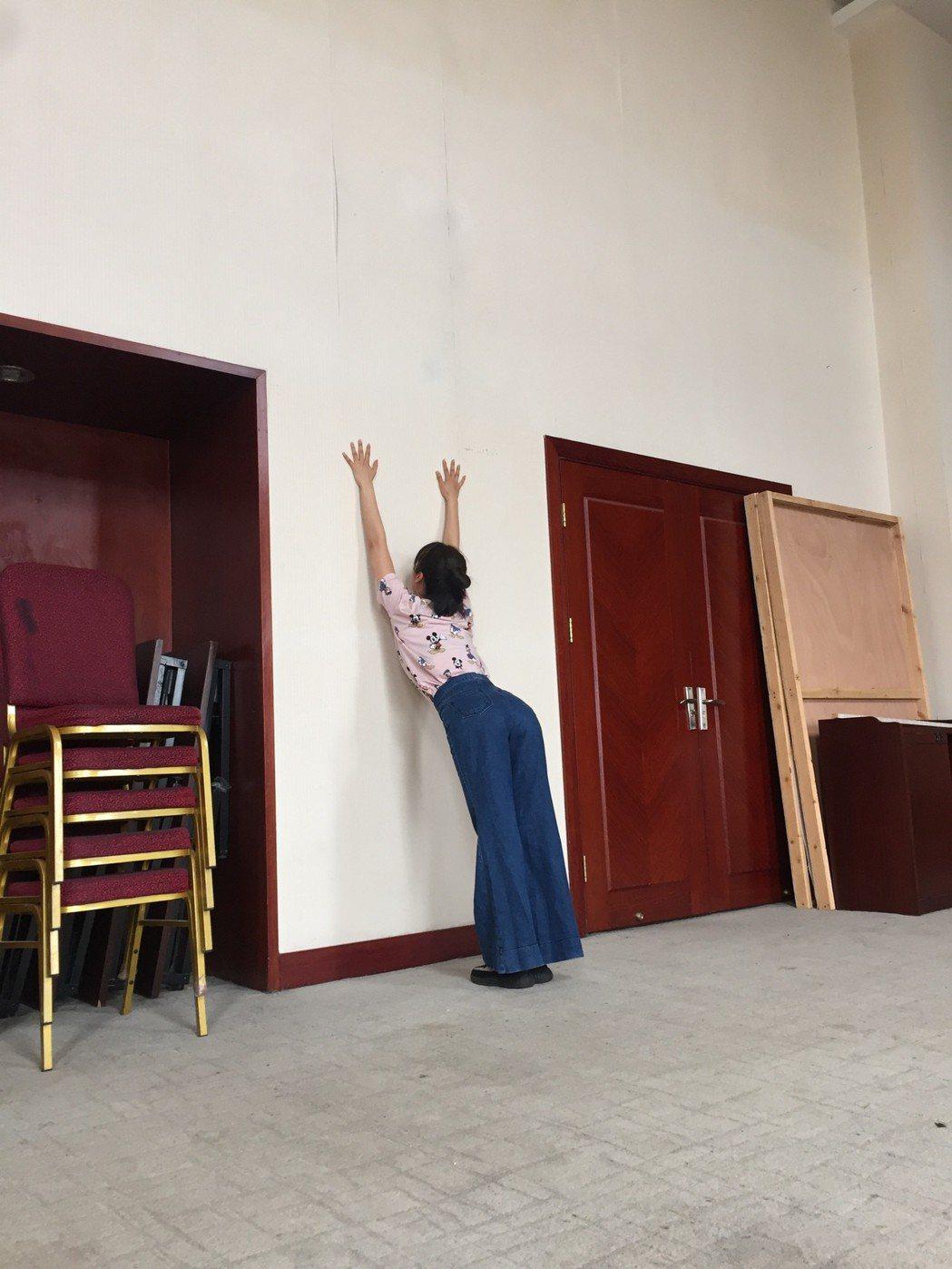 黃心娣做趴牆運動讓自己手部更柔軟。圖/周子娛樂提供