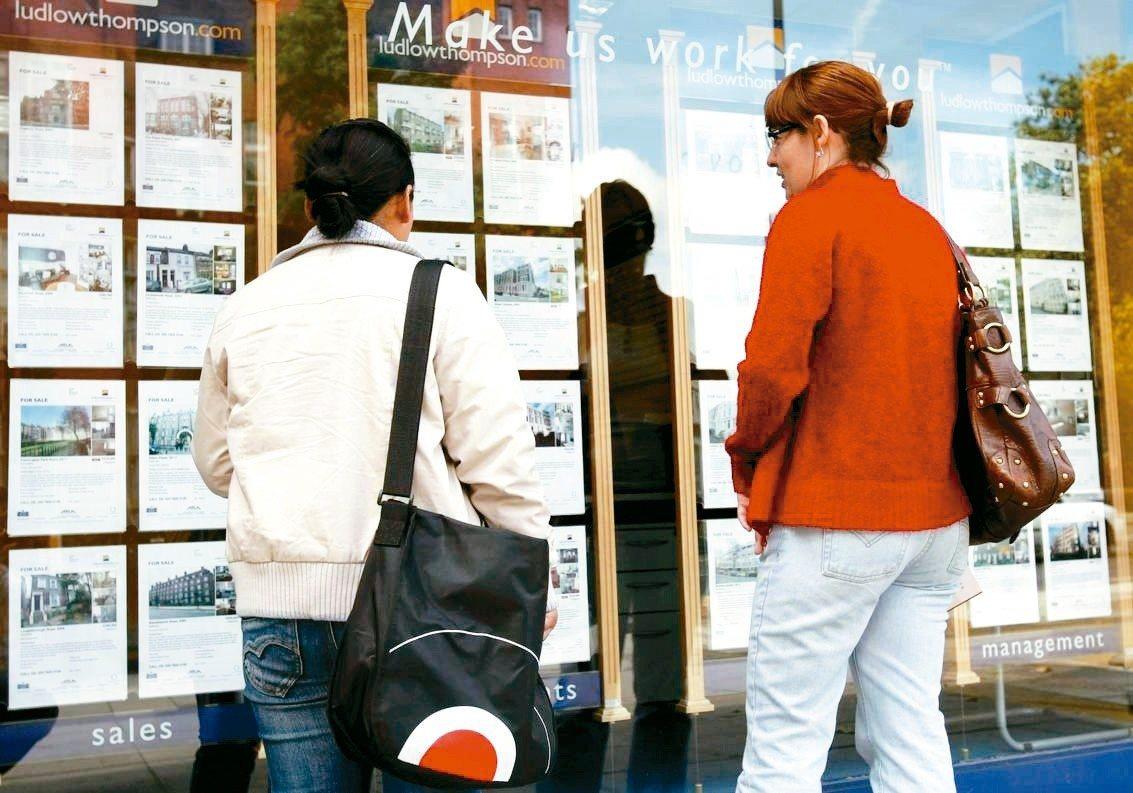 英國研究指出,兩性薪資差距在女性50歲時最大。圖為兩名女子在倫敦房屋仲介公司外看...