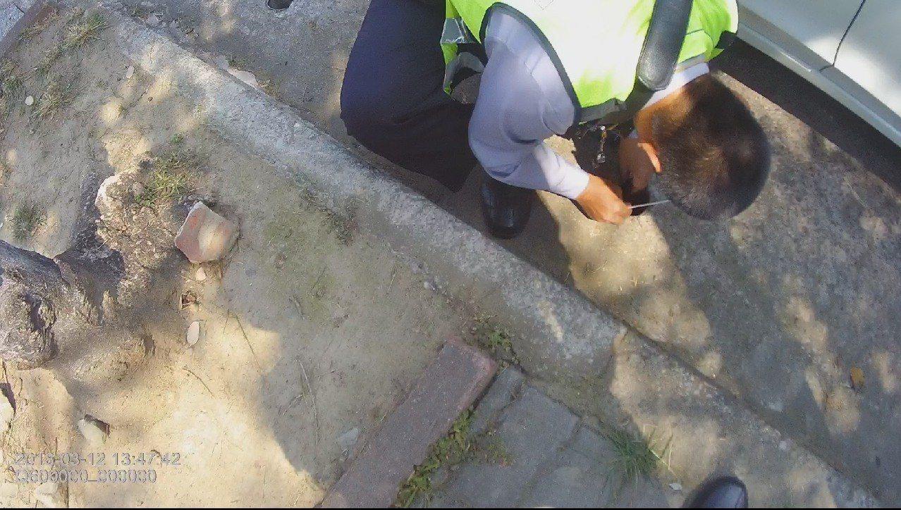 台中警察幫忙撈起,掉到10公分寬的水溝內鑰匙。記者游振昇/翻攝