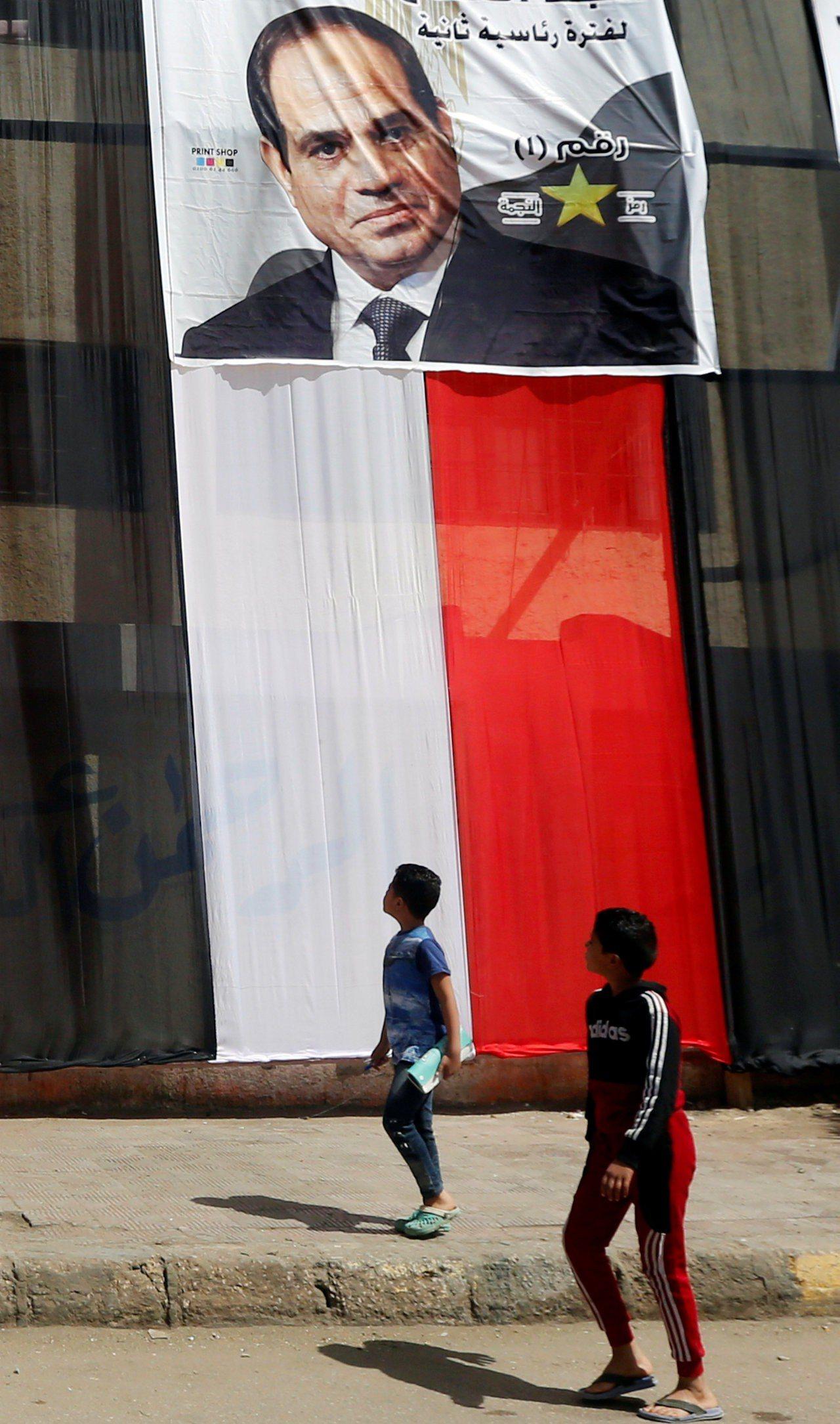 埃及首都開羅的投票所外牆25日懸掛著埃及國旗和總統塞西肖像。(路透)