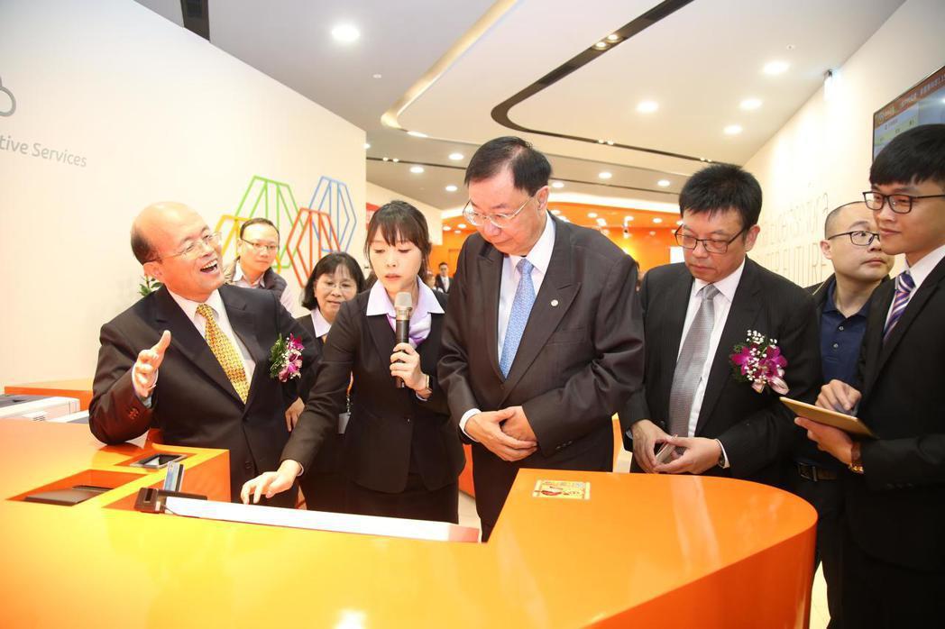 臺灣企銀董事長黃博怡(左)滿心歡喜為與會貴賓解說該數位分行特色。 毛洪霖/攝影