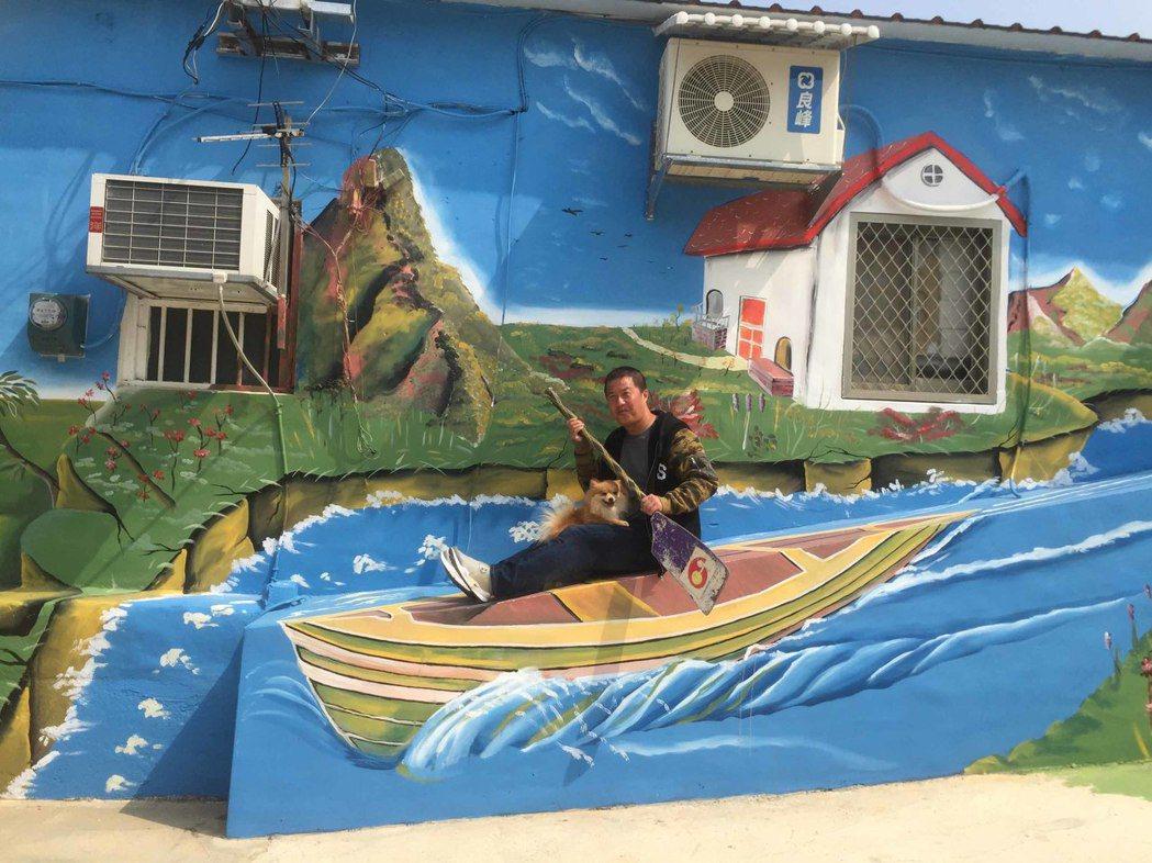 油漆工謝奇龍3D彩繪烈嶼民宅,連日來吸引不少居民和遊客前來打卡,坐在小船圖案上,...