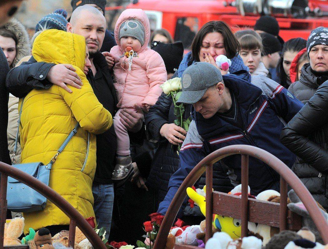 大批民眾在失火的「冬日櫻桃」商場附近擺放鮮花蠟燭為罹難者默哀。路透