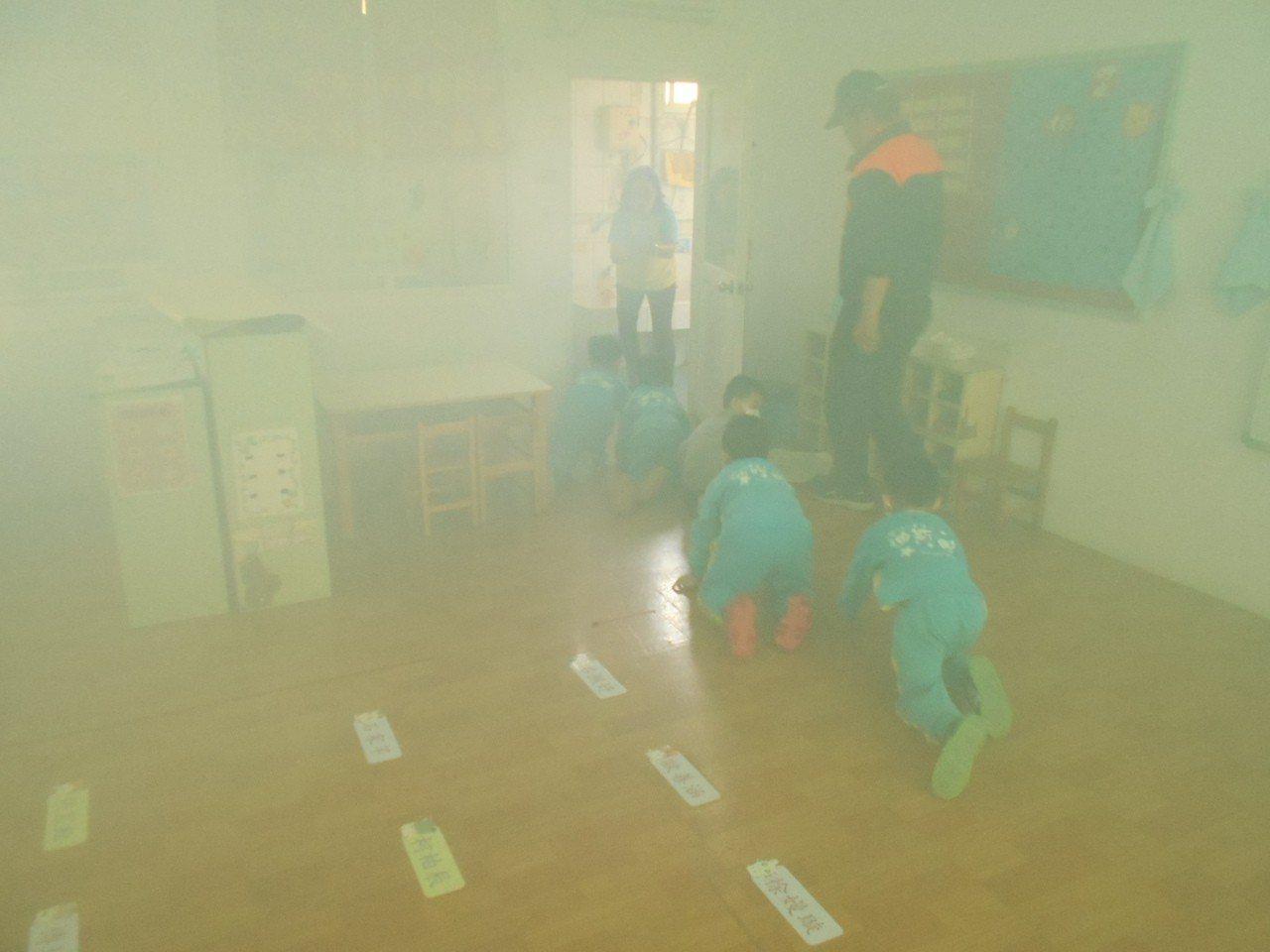 梓官消防分隊在迪斯奈幼兒園舉行防火宣導,讓幼兒體驗如遇到大火煙霧時,可採低姿式爬...