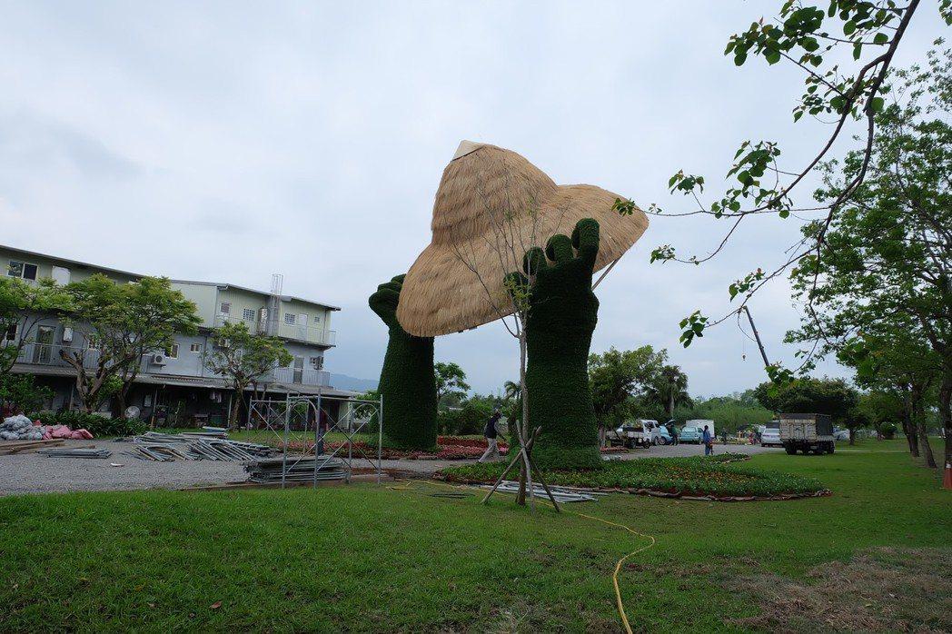 今年綠博園區的入口意象是一雙綠色巨手高舉巨大的稻草斗笠。 記者張芮瑜/攝影
