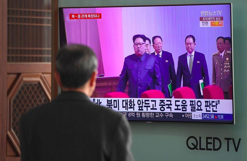 首爾車站的遊客廿七日注視電視報導北韓領導人金正恩疑似訪問北京。 (法新社)