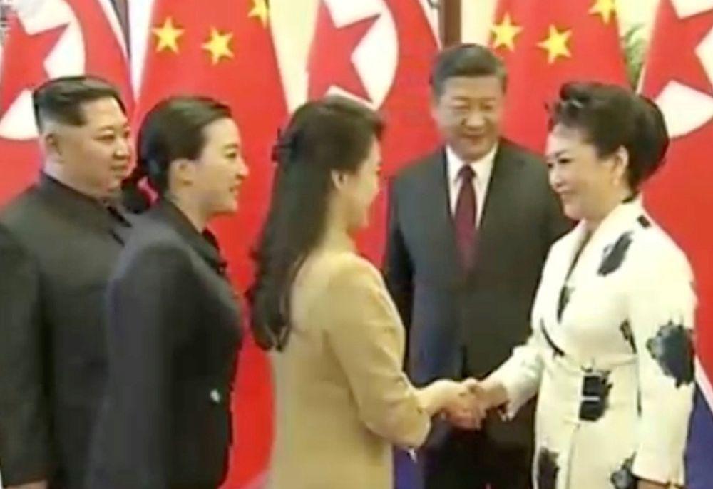 大陸第一夫人彭麗媛(右)與北韓第一夫人李雪主握手寒暄。(路透)
