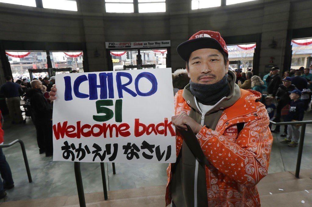 開賽前有日本球迷舉著牌子歡迎一朗回水手。 美聯社