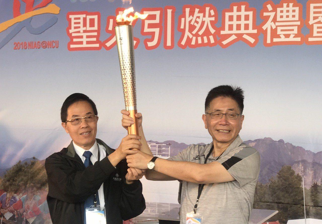 體育署副署長王水文(左)將聖火交至中央大學校長周景揚手上。記者毛琬婷/攝影