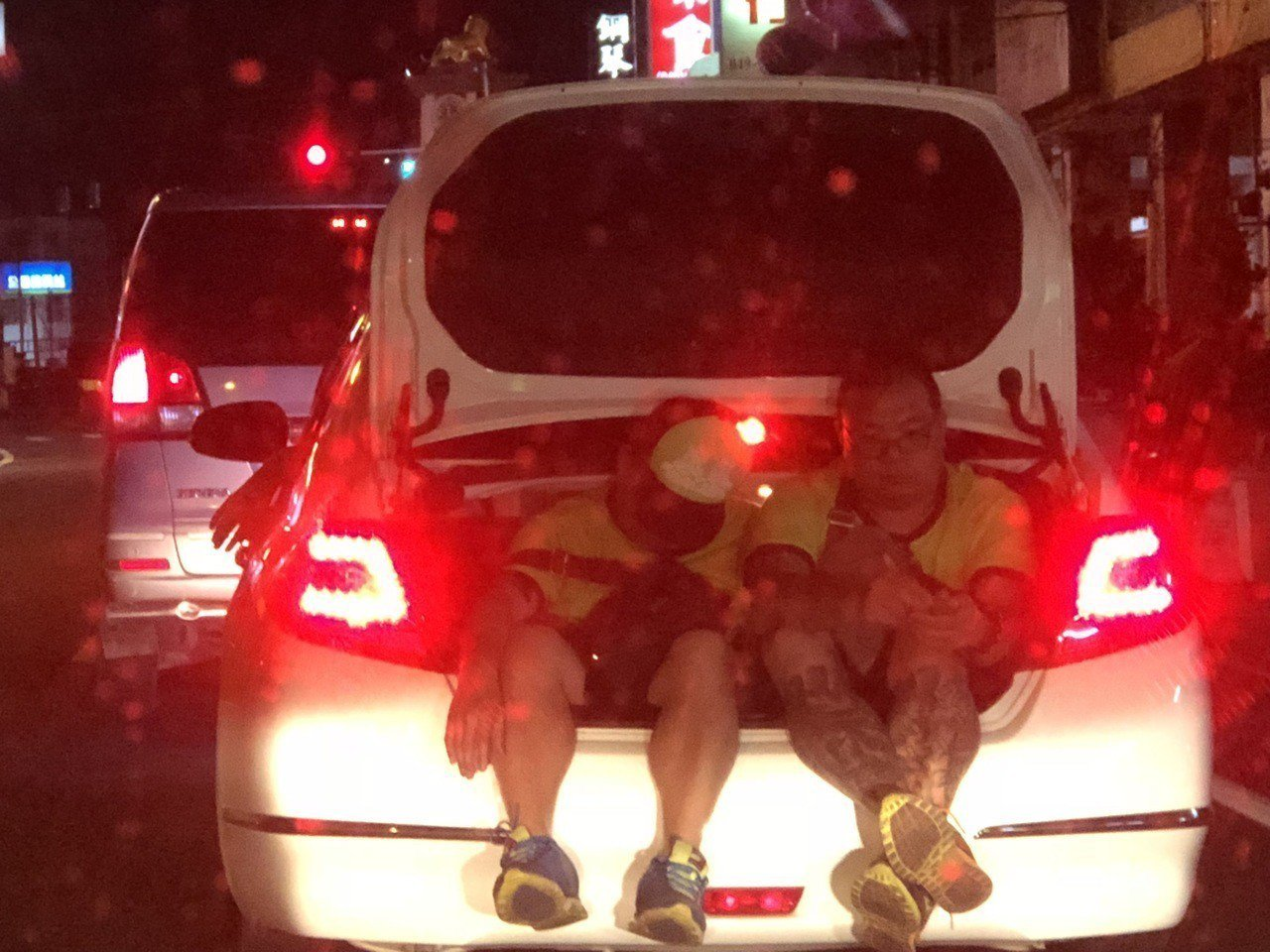 兩名男子將轎車行李廂當特別座逛南投市區,引起民眾側目。圖/張姓讀者提供