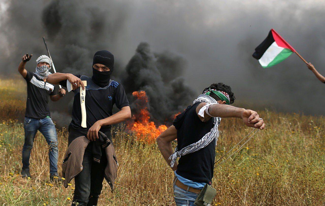 巴勒斯坦抗議民眾手持棍棒和斧頭,並投擲燃燒彈。(路透)