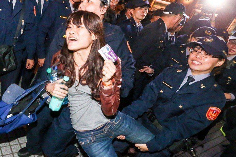 去年年底,勞團與多個學生團體反對勞基法修惡在街頭採取游擊抗爭,隨後遭警方強制排除。圖中女性為手持律師證律師,因前往現場維護民眾權益一併遭警方丟包。 圖/聯合報系資料照