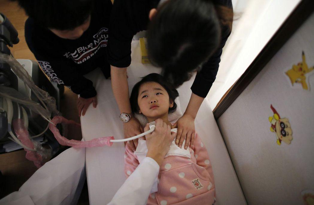 災後三年,福島縣的孩子在各方面的能力顯著下降。圖為在臨時避難住宅看醫生的孩子,攝...