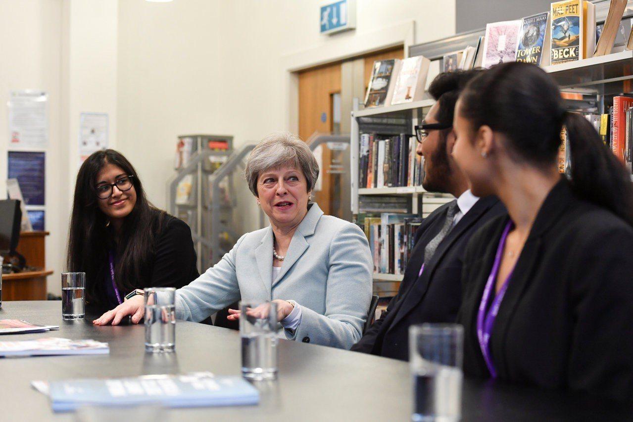 英國首相梅伊(左二)參訪中學時和教師座談檔案照。路透