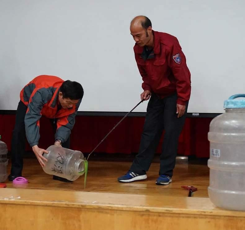 義消人員受訓,練習如何正確使用蛇勾安全捕蛇。圖/動保處提供