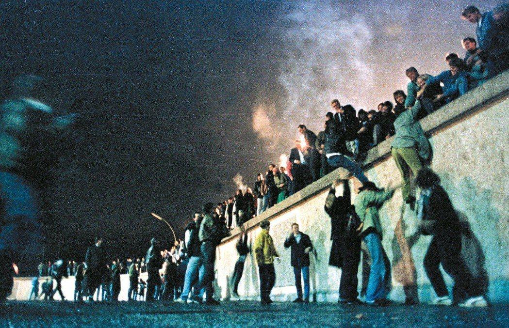 1989年11月9日,兩德民眾在東柏林邊界宣布開放後,爬上柏林圍牆慶祝。 路透資...