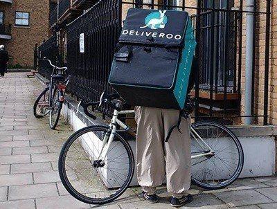 英國估計有100多萬人是零工經濟工作者,圖為一名以單車代步、背著外賣平台Deli...