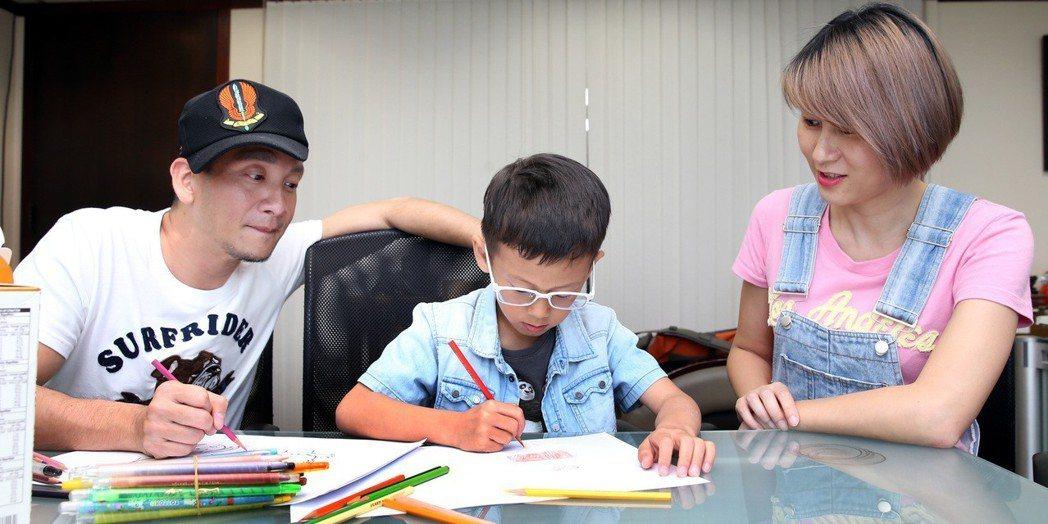 高山峰(左)與妻子佘瓊薇(右)看著兒子作畫。記者侯永全/攝影