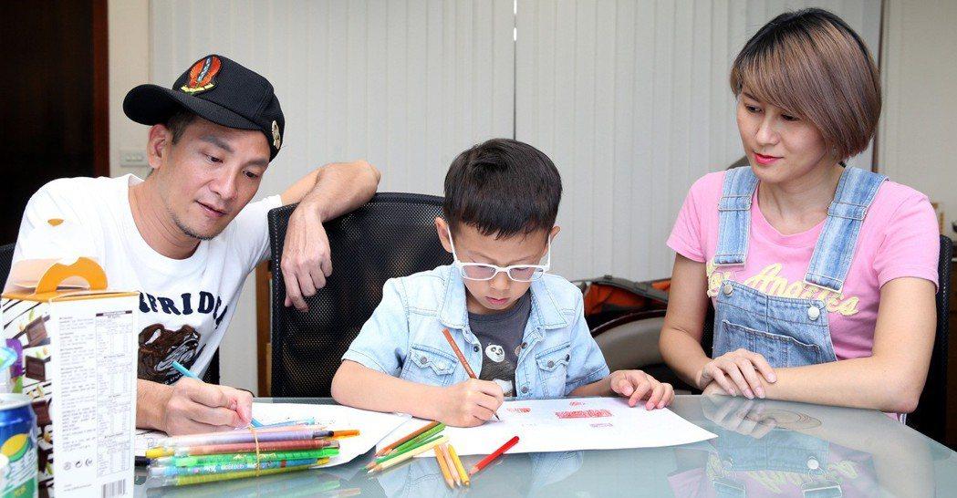 高山峰(左)與妻子佘瓊薇(右)看著兒子畫畫。記者侯永全/攝影