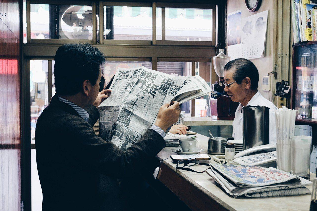 熟客們一邊看報,一邊與老闆閒話家常,構成一幅築地早市的日常畫面。記者黃仕揚/攝影