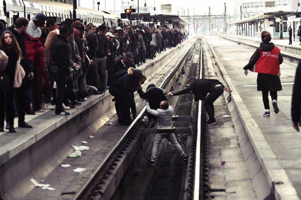 受不了排隊、欲跨越鐵軌放棄等待的法國民眾。 圖/路透社